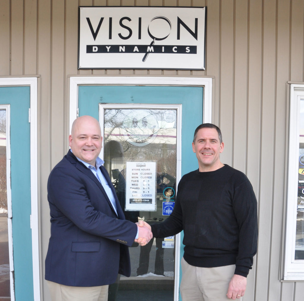 Scott Krug and Charlie Collins shake hands outside of Vision Dynamics after completed acquisition by New England Low Vision and Blindness
