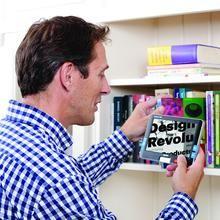Compact 7 HD man using device to read books on bookshelf