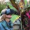 NuEyes e2 low vision electronic magnifier lady wearing in the yard