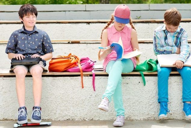 Boy using BrailleNote Touch Plus to read sitting with other students on bench