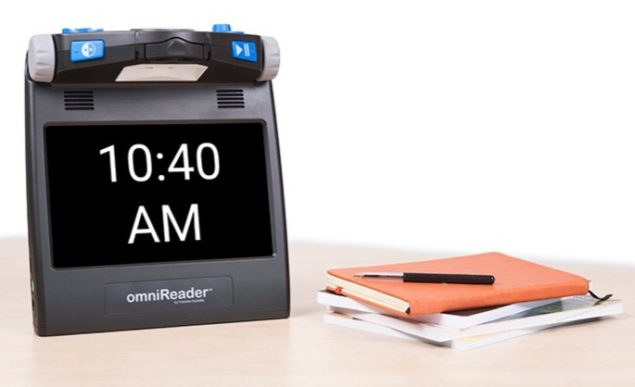 omniReader on table with books and time on monitor