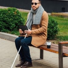 Brailliant BI 20x person sitting with white cane holding Brailliant BI 20x
