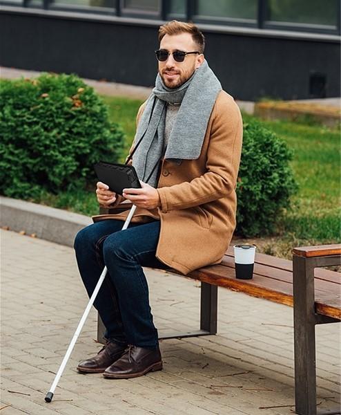 Brailliant BI 20x person sitting with white cane holding Brailliant BI 20x