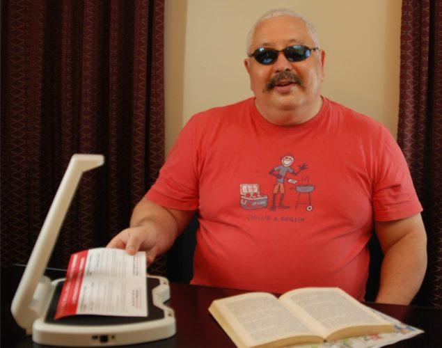 LyriQ Assistive Reader man sitting at table
